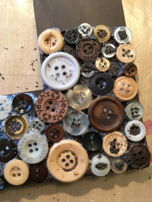 Close-up of button collage gluing