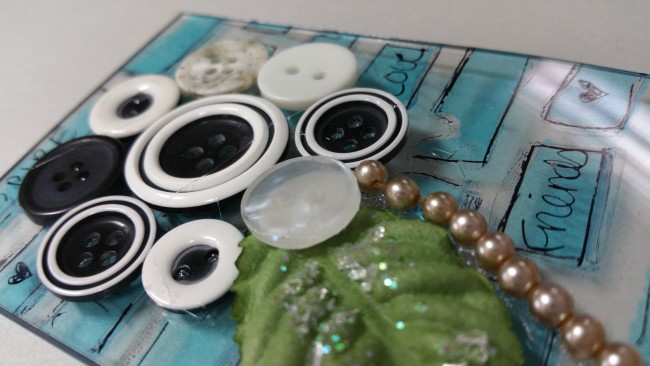 Close-up of black and white button flower ATC on a fun acrylic base.